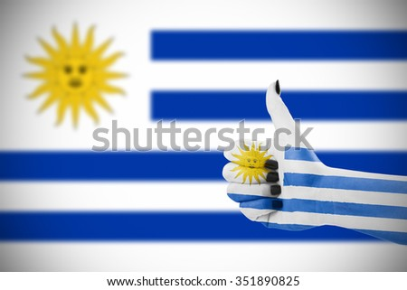 Flag of Uruguay on female's hand, second, defocused flag in background. - stock photo