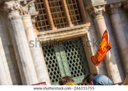 Flag of Venice with winged lion and Basilica of St. Mark's Square on background - stock photo