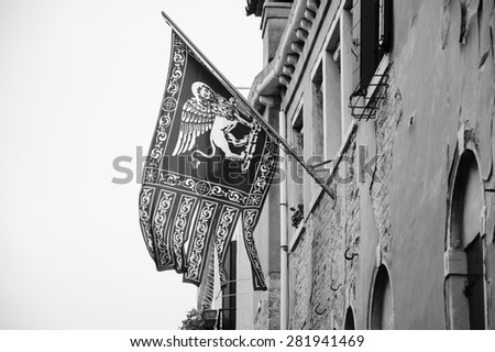 Flag of Venice with winged lion and old Venetian building on background. Cloudy winter day. Aged photo. Black and white. - stock photo