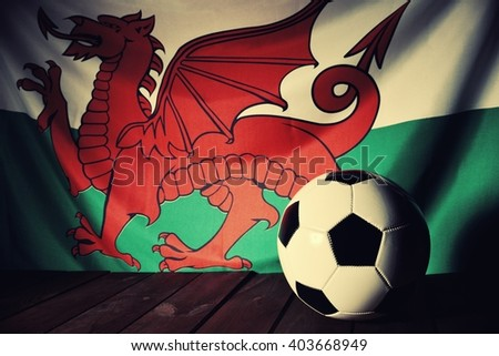 Flag of Wales with football on wooden boards as the background. Vintage Style. - stock photo