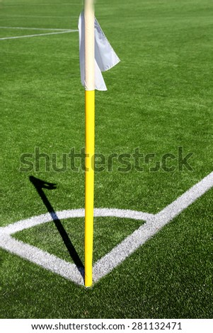 Flag on the corner of football field with shadow at sunny day - stock photo