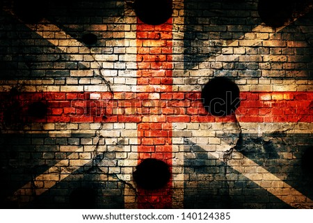 flag painted on brick wall with bullet holes - stock photo