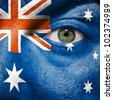 Flag painted on face with green eye to show Australia support in sport matches - stock photo