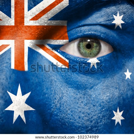 Flag painted on face with green eye to show Australia support in sport matches