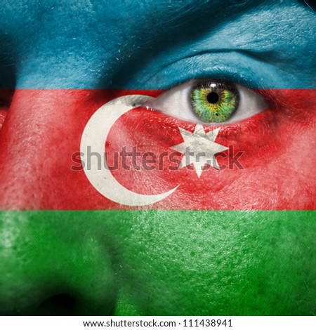 Flag painted on face with green eye to show Azerbaijan support - stock photo