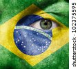 Flag painted on face with green eye to show Brazil support in sport matches - stock photo