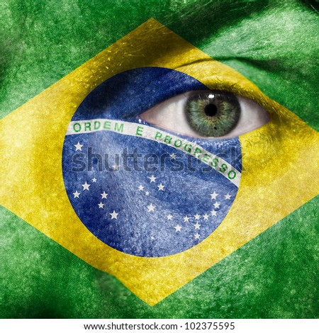 Flag painted on face with green eye to show Brazil support in sport matches