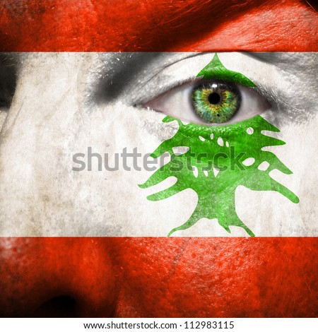 Flag painted on face with green eye to show Lebanon support - stock photo