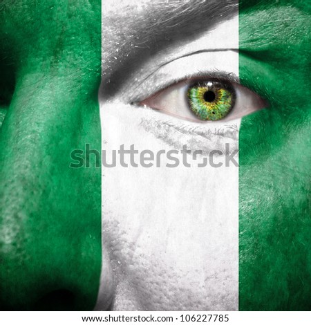 Flag painted on face with green eye to show nigeria support - stock photo