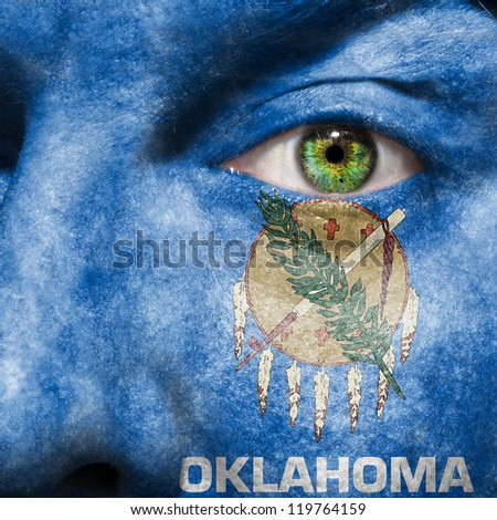 Flag painted on face with green eye to show Oklahoma support - stock photo
