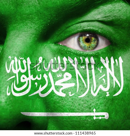 Flag painted on face with green eye to show Saudi Arabia support