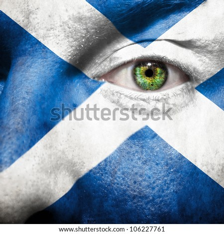 Flag painted on face with green eye to show Scotland support - stock photo