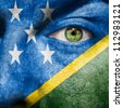 Flag painted on face with green eye to show Solomon Islands support - stock photo