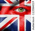 Flag painted on face with green eye to show UK support - stock photo