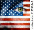 Flag painted on face with green eye to show USA support - stock photo