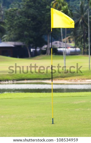 flag pole in hole of a golf course. - stock photo