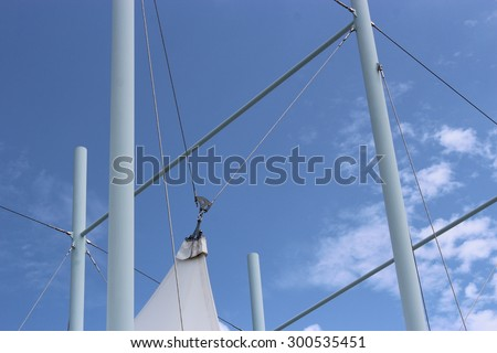 Flag pole with ropes and tent sail against blue cloudy sky