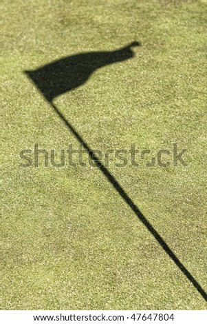 Flag shadow on a golf field, without ball - stock photo