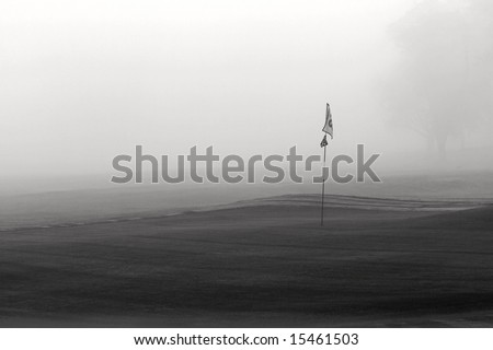 Flag stick on golf course putting green during a foggy morning. - stock photo