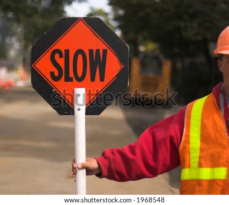 "Flagger directing traffic, holding ""Slow"" sign - stock photo"