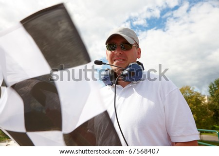 Flagman with checkered flag meaning that winner has just crossed the finish line.