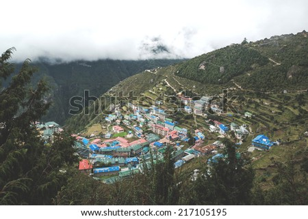 flags and the town of Namche Bazaar in Nepal  - stock photo
