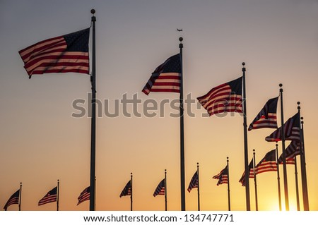 Flags around the base of the Washington Monument at sunset