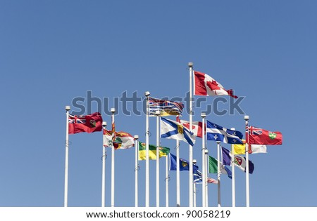 Flags flying in the Wind - Flags of the Canadian Provinces on Canada Place, Vancouver, British Columbia, Canada - stock photo