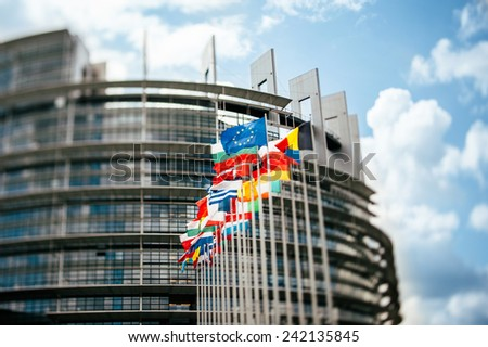 Flags in front of the European Parliament, Flags in front of the European Parliament, Strasbourg, France.  Tilt shift lens used to accent the flags and sublime toned filter applied for more effect - stock photo