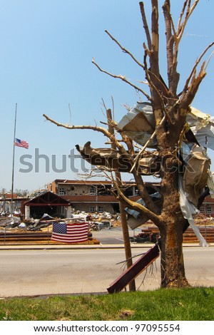 Flags in Joplin, Mo flew at half mast for weeks after an EF-5 tornado which left a trail of death and destruction nearly 7 miles long and up to a half mile wide in during the spring of 2011. - stock photo