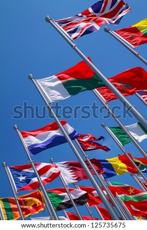 Flags of all nations of the world are flying in blue sunny sky - stock photo