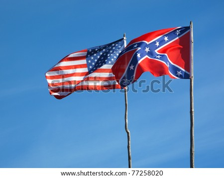 Flags of American civil war. Union flag and Confederate flag under blue sky. - stock photo