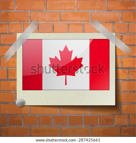 Flags of Canada scotch taped to a red brick wall.  Rasterized version - stock photo