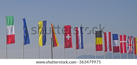 Flags of different countries against blue sky - stock photo
