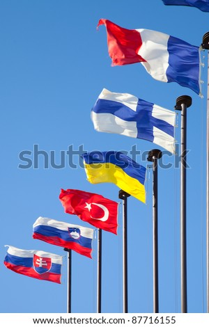 Flags of different countries are developing on the flagpoles - stock photo