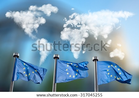 Flags of European Union with world map made of clouds against European Parliament in Brussels, Belgium - stock photo