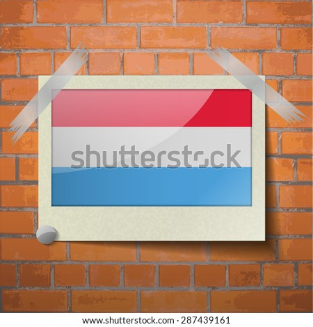 Flags of Luxembourg scotch taped to a red brick wall.  Rasterized version - stock photo