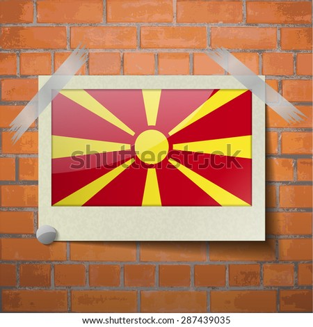 Flags of Macedonia scotch taped to a red brick wall.  Rasterized version - stock photo