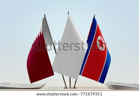 Flags of Qatar and North Korea with a white flag in the middle