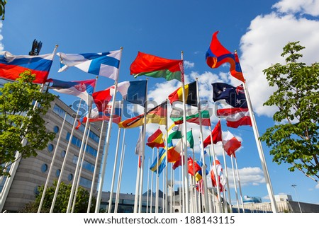 Flags of the different countries on flagstaffs against the sky - stock photo