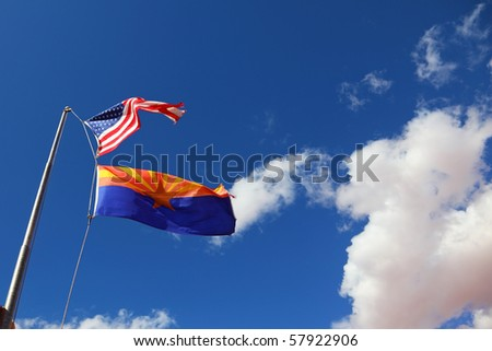 Flags of the United States and the Navajo Reservation are flying against the clouds - stock photo