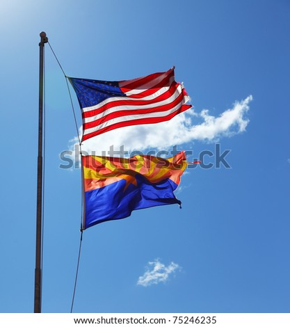 Flags of the United States and the Navajo Reservation are flying against the shining sun and clouds - stock photo