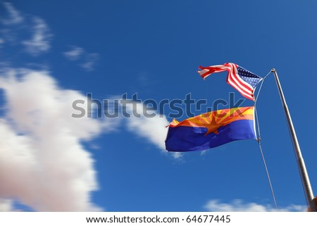 Flags of the United States and the Navajo Reservation are flying in the strong wind - stock photo