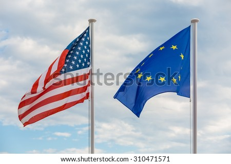 Flags of United States of America and European Union hanging on poles, waving in the wind - stock photo