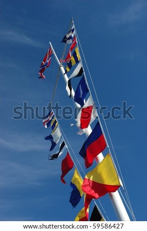 Flags. /  On a flagstaff multi-colored flags against the dark blue sky develop on a wind.