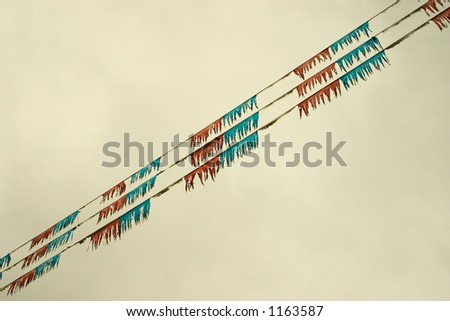 Flags on a used car lot in a diaganol direction across the image - stock photo