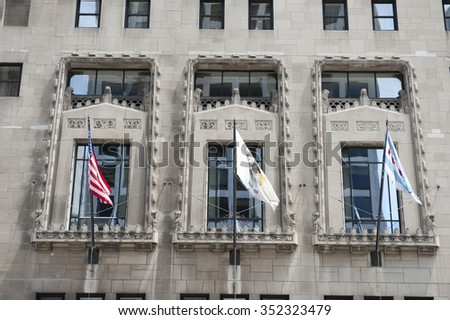 Flags on the Chicago Tribune Tower building in Chicago. Chicago Tribune tower is a tall skyscraper in Chicago, which is home to Chicago Tribune, Tribune Publishing and Tribune Media. - stock photo