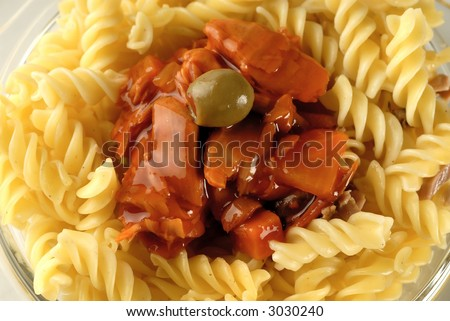 Flaked tuna in a tomato sauce on a noodle and olive on it - stock photo