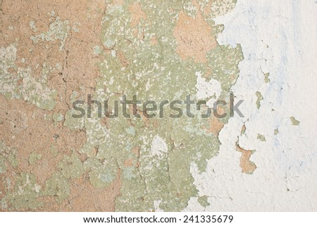 Flaking old rendered tan light green white cream painted wall - stock photo
