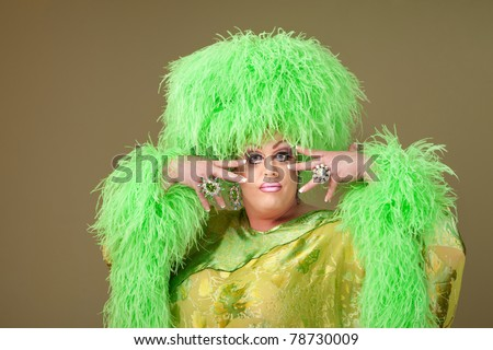 Flamboyant drag queen in boa hat on green background
